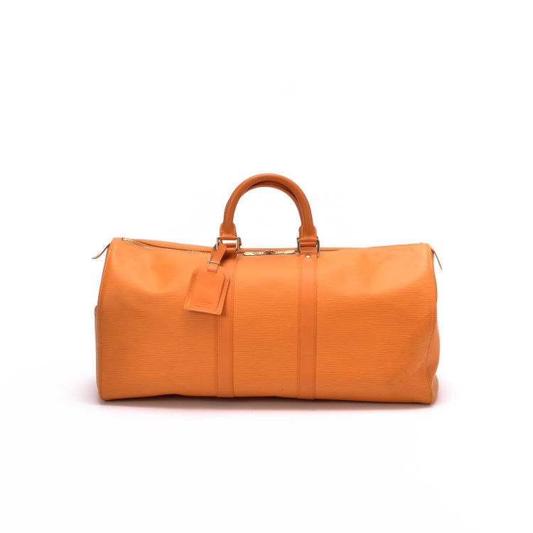 LXRandCo guarantees this is an authentic vintage Louis Vuitton Keepall 45  travel bag. This stylish carry on was crafted in epi leather in beautiful  orange. 3aab281091dd9