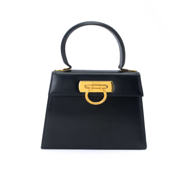 edb0f7f52d27 LXRandCo guarantees the authenticity of this vintage Ferragamo Top Handle  handbag. This classic handbag in navy is made in gancini calf.