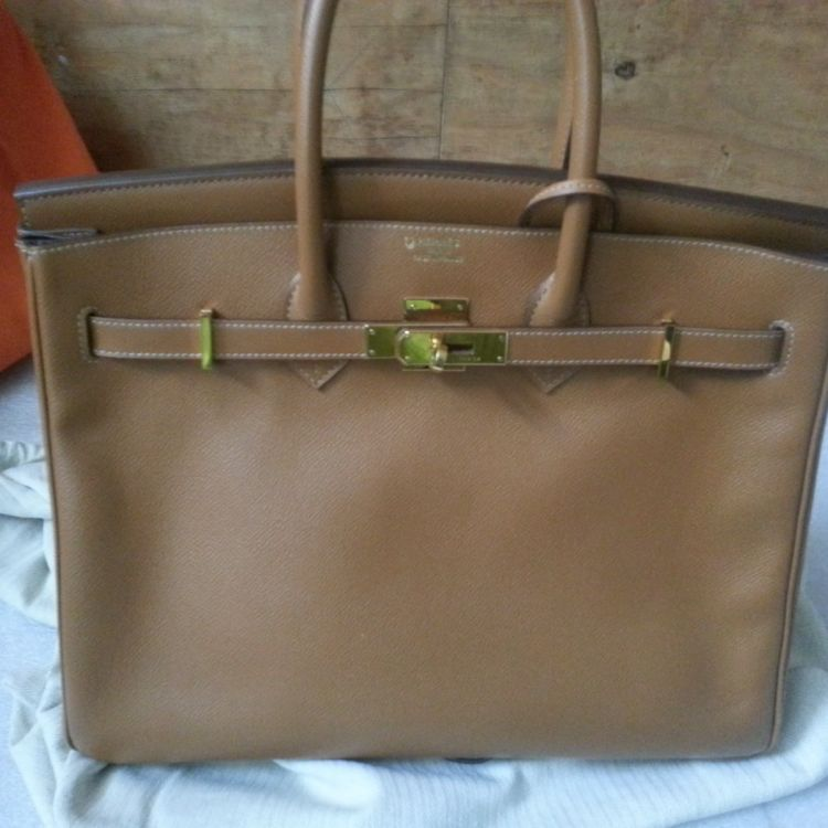 2323c780c1 LXRandCo guarantees the authenticity of this vintage Hermès Birkin 35  Horseshoe Gold and Brown GHW handbag. This practical handbag in beautiful  gold is made ...