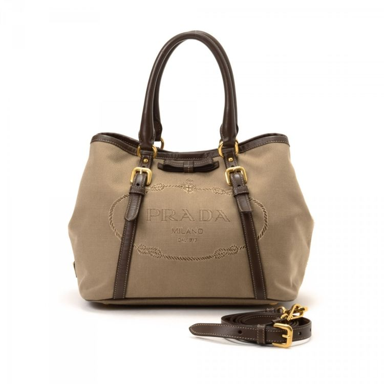 0fa750ac596 LXRandCo guarantees the authenticity of this vintage Prada Jacquard Logo  Two Way Bag handbag. This stylish pocketbook comes in beige canvas.