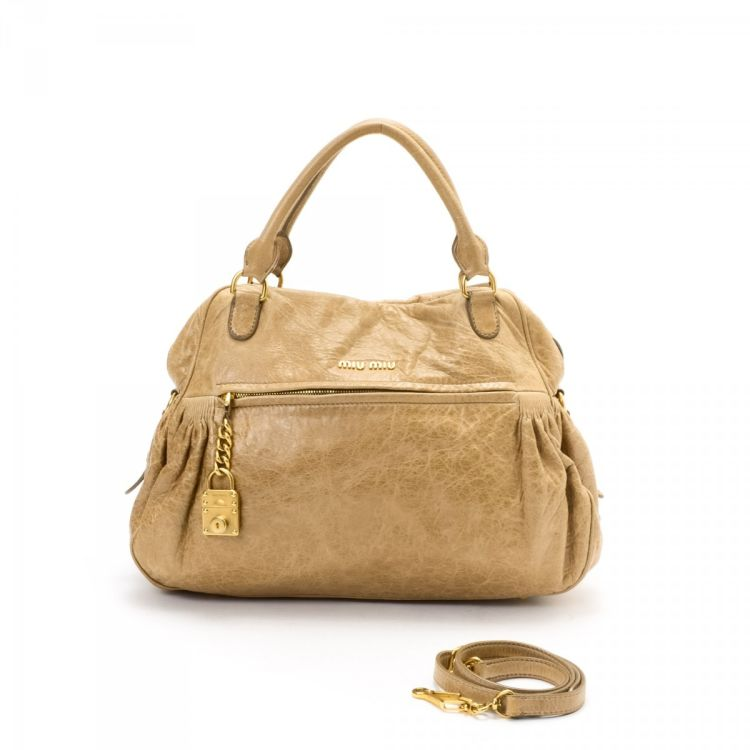 4ec1819bc723 The authenticity of this vintage Miu Miu Nappa Charm Two Way Bag handbag is  guaranteed by LXRandCo. This exquisite purse comes in beautiful beige calf.