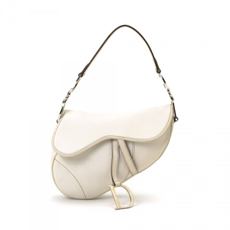 a51f09fca14 LXRandCo guarantees the authenticity of this vintage Dior Saddle Bag  shoulder bag. This sophisticated shoulder bag comes in white leather.
