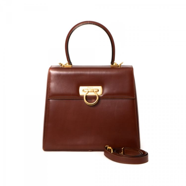 ad13f19b0246 LXRandCo guarantees the authenticity of this vintage Ferragamo Top Handle  handbag. This classic handbag was crafted in gancini leather in brown.
