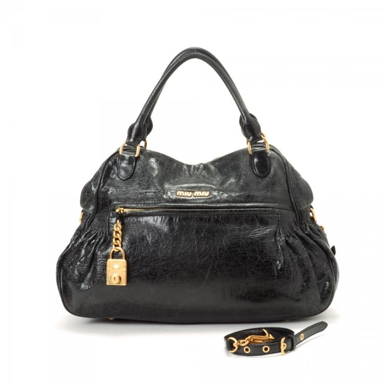 6a5e4f7e703 The authenticity of this vintage Miu Miu Nappa Charm Two Way Bag handbag is  guaranteed by LXRandCo. This classic handbag was crafted in calf in black.
