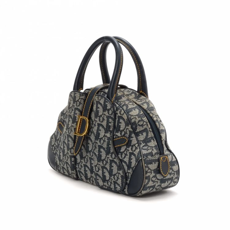 f626e9773 The authenticity of this vintage Dior Saddle Bowling Mini Bag handbag is  guaranteed by LXRandCo. This luxurious bag in navy is made in trotter canvas .