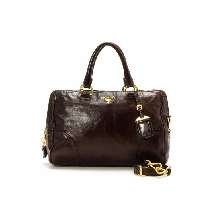 be2a5ff1ba15 The authenticity of this vintage Prada Two Way Bag handbag is guaranteed by  LXRandCo. This refined purse comes in beautiful brown leather.