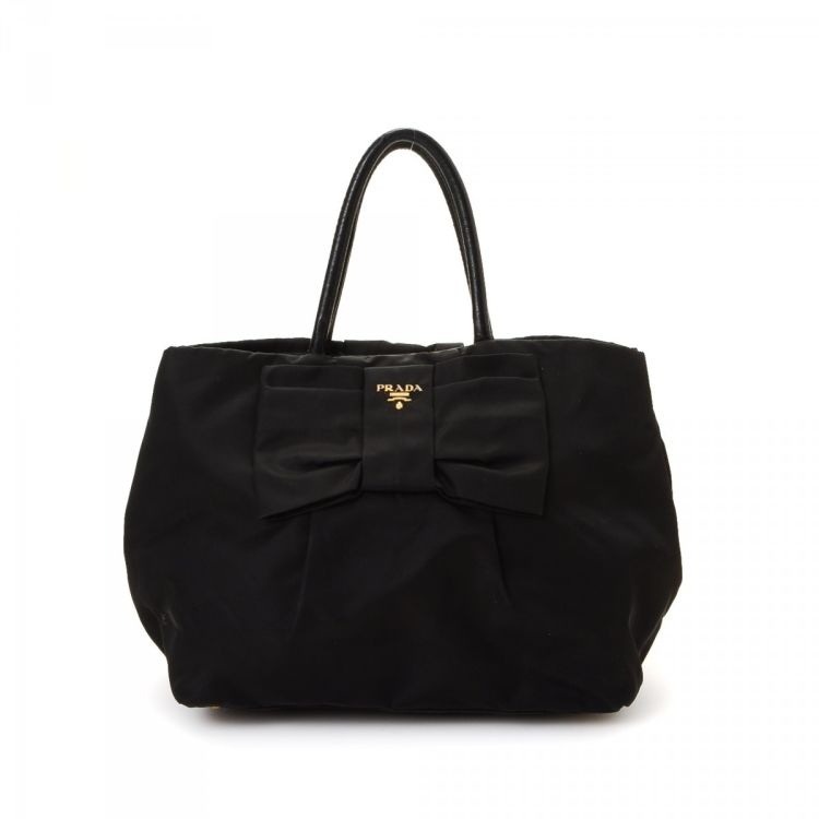 0b70cd8cef30 LXRandCo guarantees the authenticity of this vintage Prada Tessuto Bow  handbag. This lovely purse in beautiful black is made of nylon.