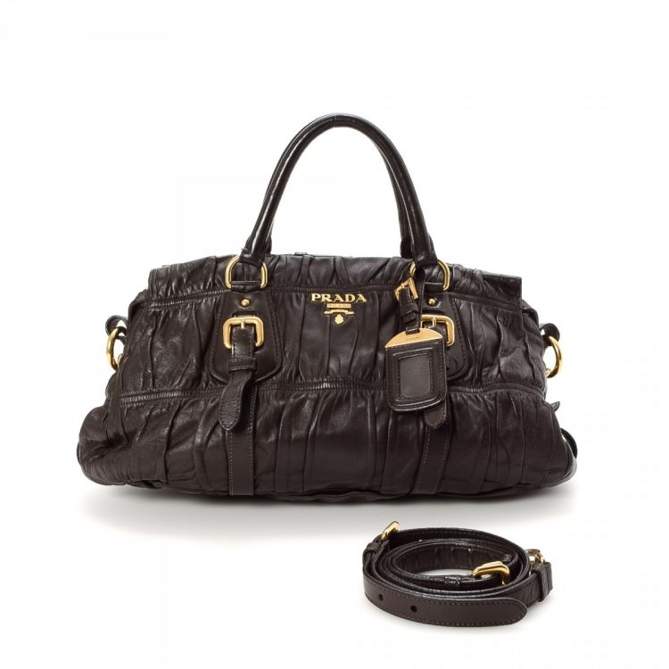 7219eb7c0612 The authenticity of this vintage Prada Two Way Bag Ruched Bag handbag is  guaranteed by LXRandCo. This everyday pocketbook comes in dark brown leather .