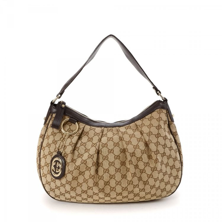 ac6623335fd The authenticity of this vintage Gucci Sukey Hobo Bag shoulder bag is  guaranteed by LXRandCo. This signature pocketbook in beige is made in gg  canvas.