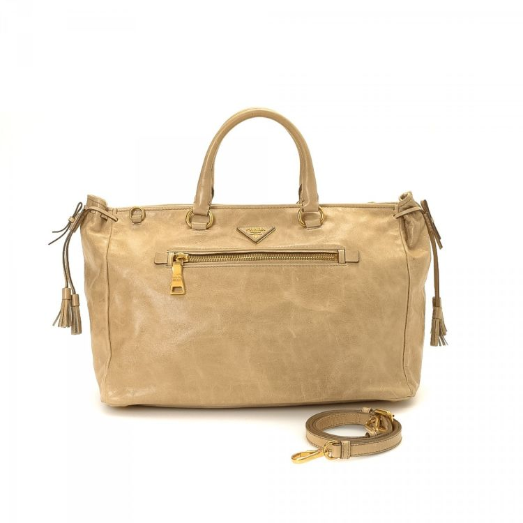 5dc1950cea33 LXRandCo guarantees the authenticity of this vintage Prada Two Way Bag tote.  This elegant tote bag in beige is made of leather. Due to the vintage  nature of ...