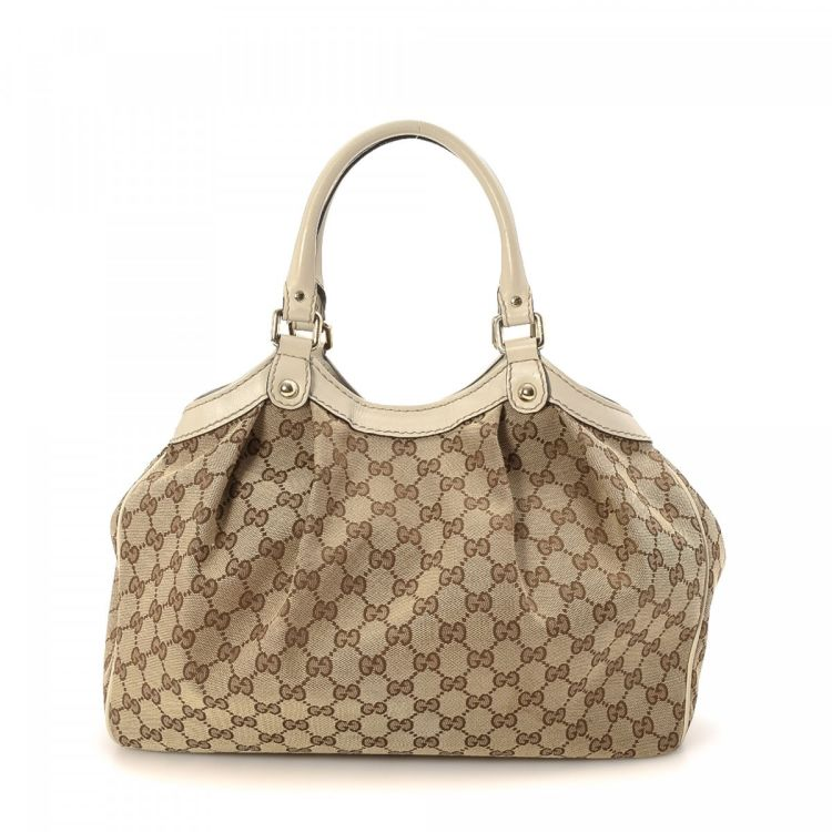 c17a2067b LXRandCo guarantees the authenticity of this vintage Gucci Sukey Medium tote.  Crafted in gg canvas, this luxurious large handbag comes in beautiful brown.