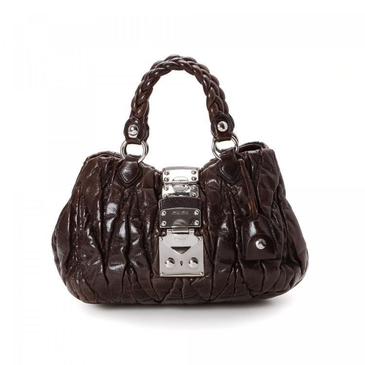 c7c7823f04d1 The authenticity of this vintage Miu Miu Coffer Bag handbag is guaranteed  by LXRandCo. This stylish purse was crafted in matelasse leather in  beautiful dark ...