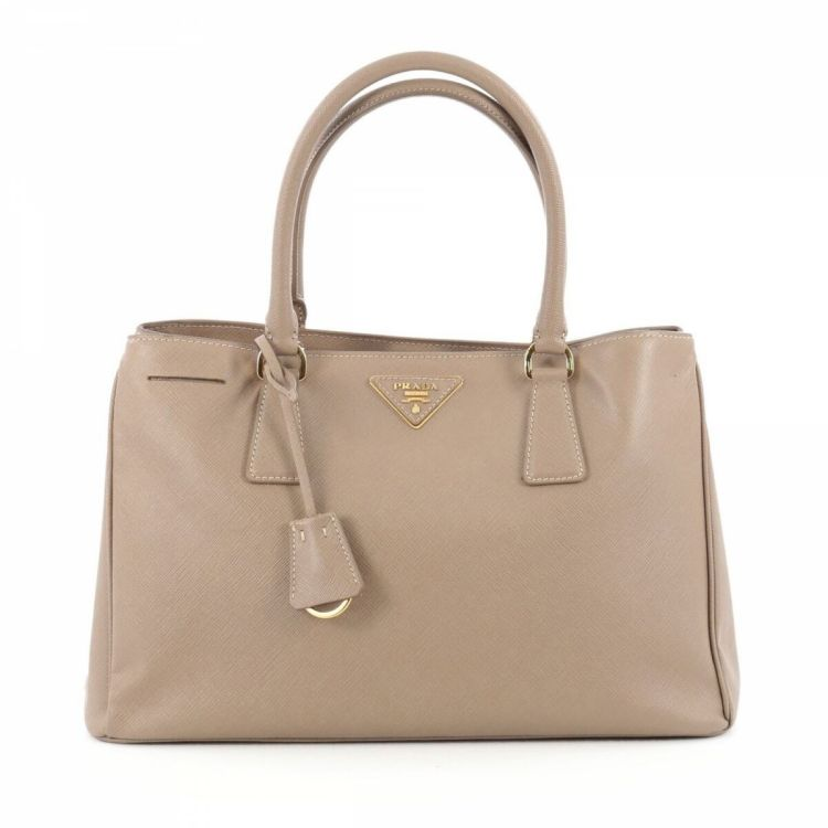 42c1c64d7fdf3 LXRandCo guarantees the authenticity of this vintage Prada Gardener s tote.  This practical work bag in beautiful beige is made in saffiano leather.