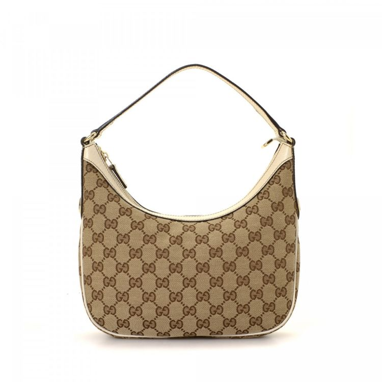 3441addb685 The authenticity of this vintage Gucci handbag is guaranteed by LXRandCo.  This classic purse was crafted in gg canvas in beige. Due to the vintage  nature of ...