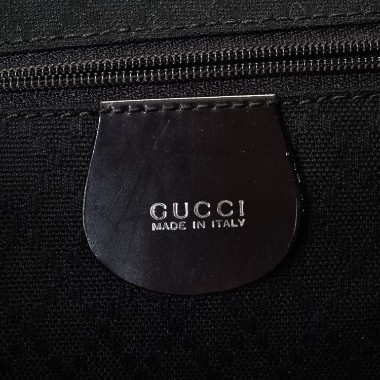 LXRandCo guarantees the authenticity of this vintage Gucci backpack. This signature  book bag in beautiful black is made in bamboo nylon. 5060cded21901