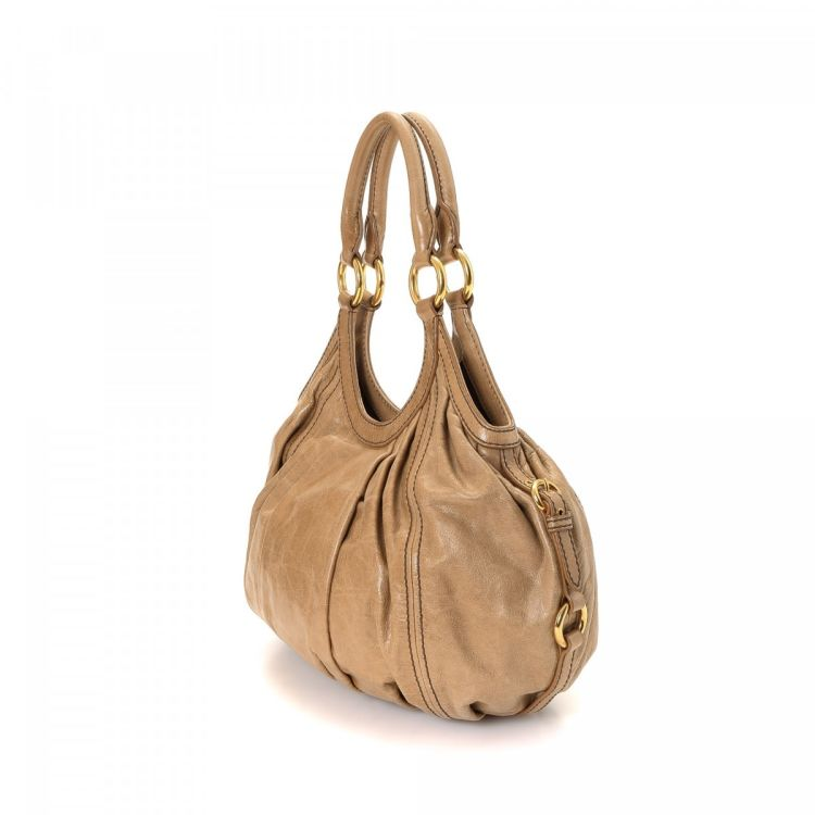 4325b2be758f LXRandCo guarantees the authenticity of this vintage Miu Miu Hobo Bag  shoulder bag. This sophisticated bag was crafted in leather in tan.