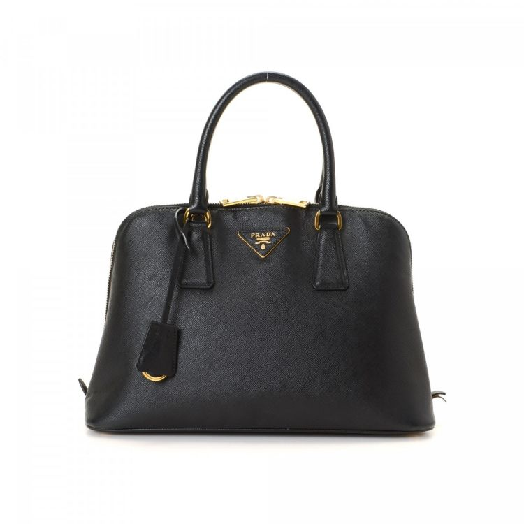 01369b5633c326 LXRandCo guarantees the authenticity of this vintage Prada handbag. Crafted  in saffiano cross-grain leather, this beautiful pocketbook comes in black.