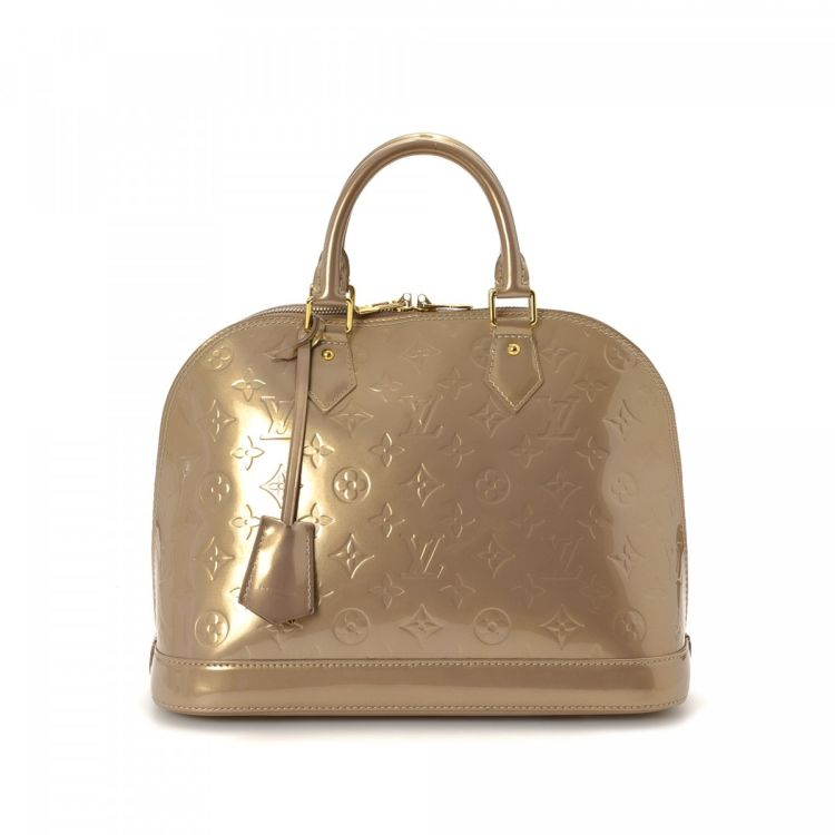 6551563e81b1 LXRandCo guarantees the authenticity of this vintage Louis Vuitton Alma  handbag. This everyday pocketbook in beige poudre is made in vernis patent  leather.