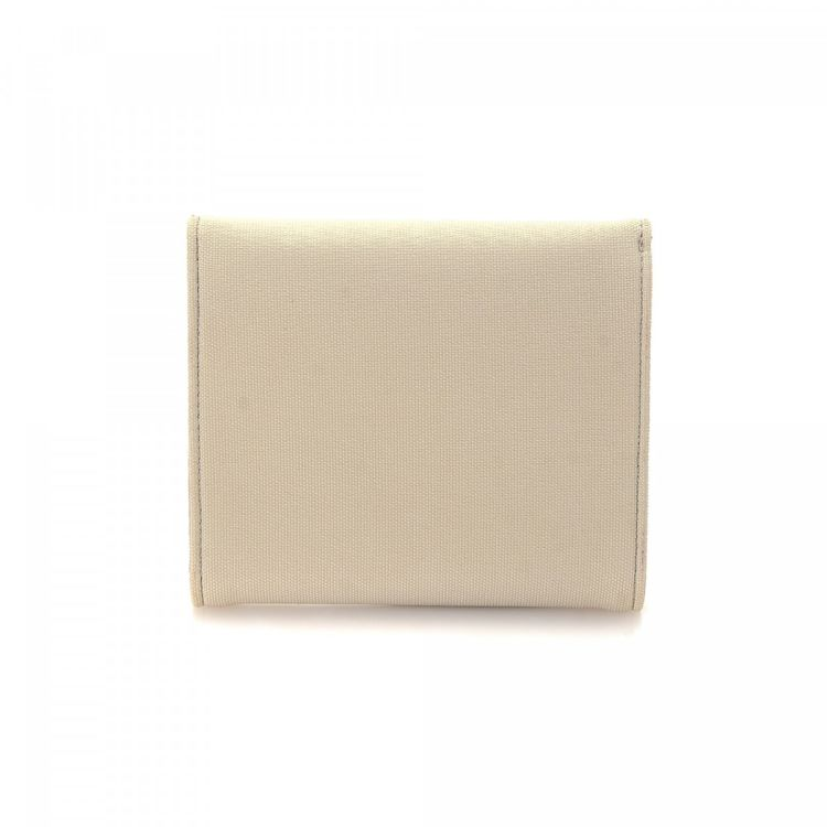 ee0269bd6ea LXRandCo guarantees the authenticity of this vintage Ferragamo wallet. This  practical bifold in beautiful cream is made of canvas. Due to the vintage  nature ...
