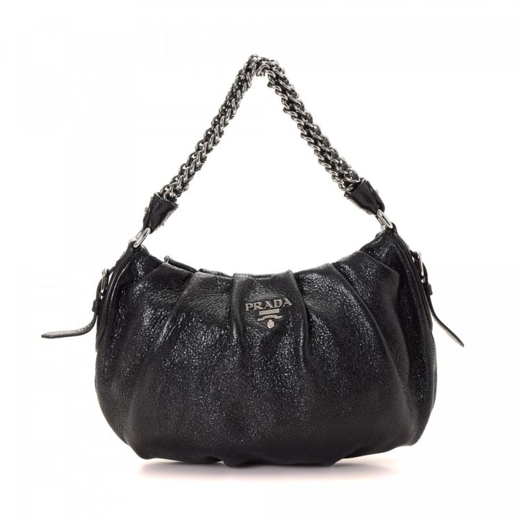 af86f7092571 The authenticity of this vintage Prada handbag is guaranteed by LXRandCo.  This practical bag in black is made in vitello daino calf.