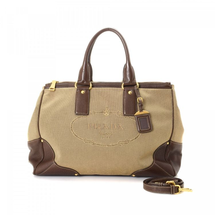 ab95718708e LXRandCo guarantees the authenticity of this vintage Prada Logo travel bag.  Crafted in jacquard canvas, this lovely boston bag comes in beige.