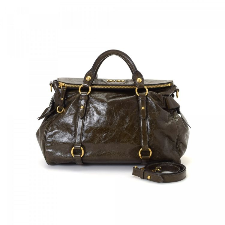 9abd96aee06 LXRandCo guarantees this is an authentic vintage Miu Miu Bow handbag. This  refined purse was crafted in vitello leather in dark green.