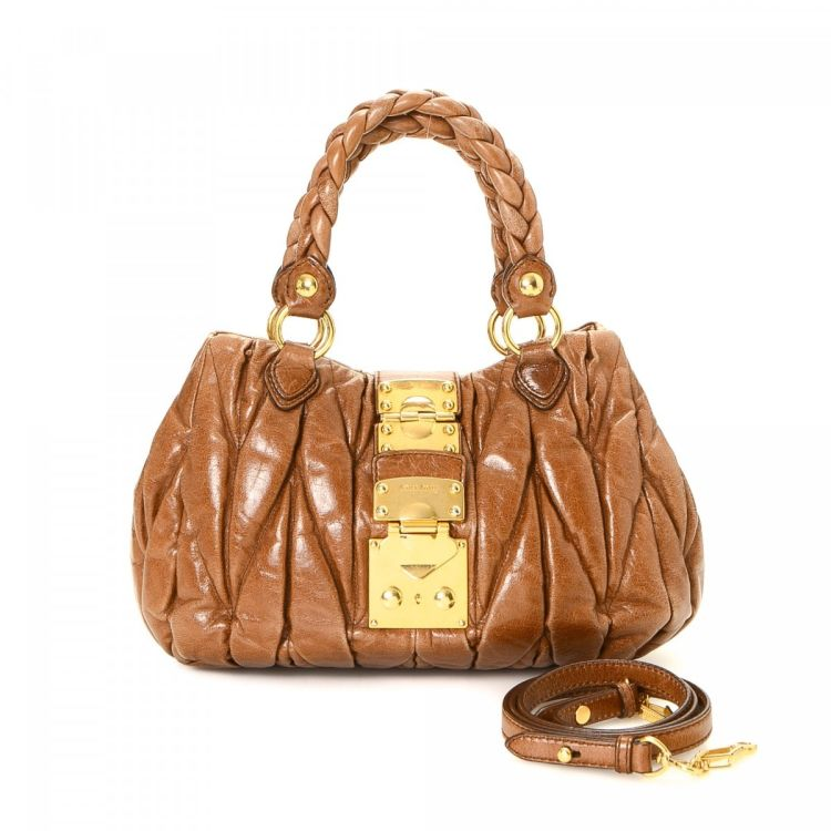 eac706a71a44 LXRandCo guarantees the authenticity of this vintage Miu Miu Coffer Bag  handbag. This signature pocketbook in brown is made in matelasse leather.
