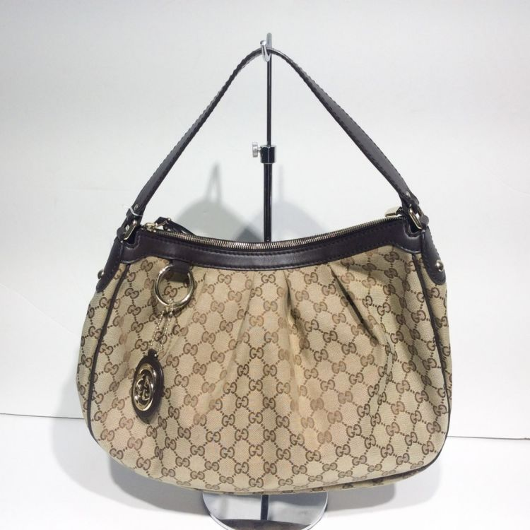 ae422527747 LXRandCo guarantees the authenticity of this vintage Gucci Sukey Medium Hobo  shoulder bag. This iconic shoulder bag was crafted in gg canvas in beige.