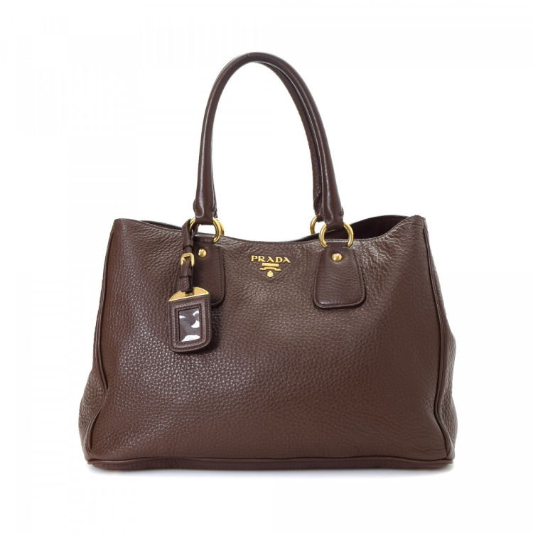 f583875b6596 The authenticity of this vintage Prada tote is guaranteed by LXRandCo. This  everyday tote bag in beautiful brown is made in vitello daino leather.