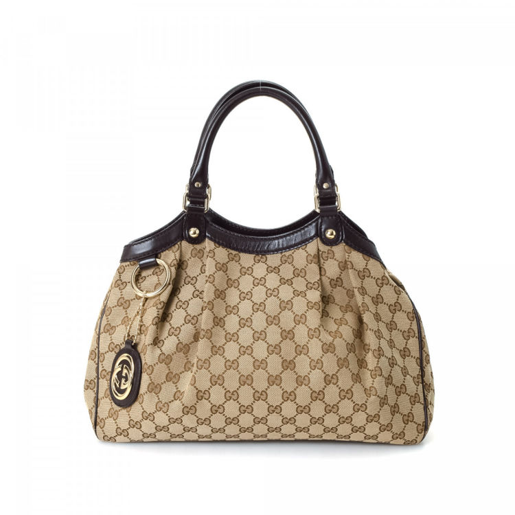 a9b8037fe883 The authenticity of this vintage Gucci Sukey tote is guaranteed by LXRandCo.  This sophisticated tote in beautiful beige is made in gg canvas.