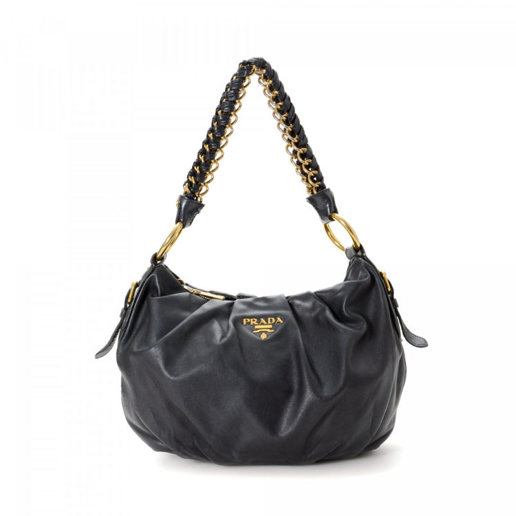 af410cdbe289 The authenticity of this vintage Prada Hobo shoulder bag is guaranteed by  LXRandCo. Crafted in nappa leather, this lovely purse comes in beautiful  black.