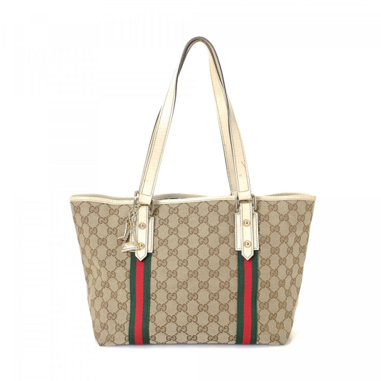 49dffd521ba LXRandCo guarantees the authenticity of this vintage Gucci tote. This  classic tote was crafted in gg canvas in beige. Due to the vintage nature  of this ...