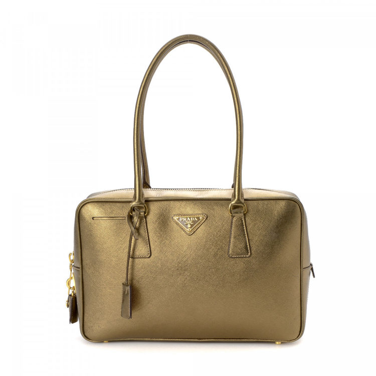 The authenticity of this vintage Prada handbag is guaranteed by LXRandCo.  This iconic bag was crafted in saffiano leather in gold. Due to the vintage  nature ... eed4989791da7