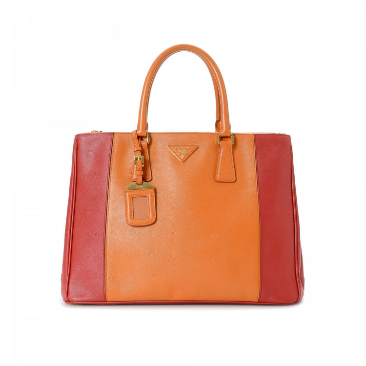 LXRandCo guarantees this is an authentic vintage Prada handbag. This lovely  bag was crafted in saffiano leather in beautiful two-tone. 54a1c653d9104