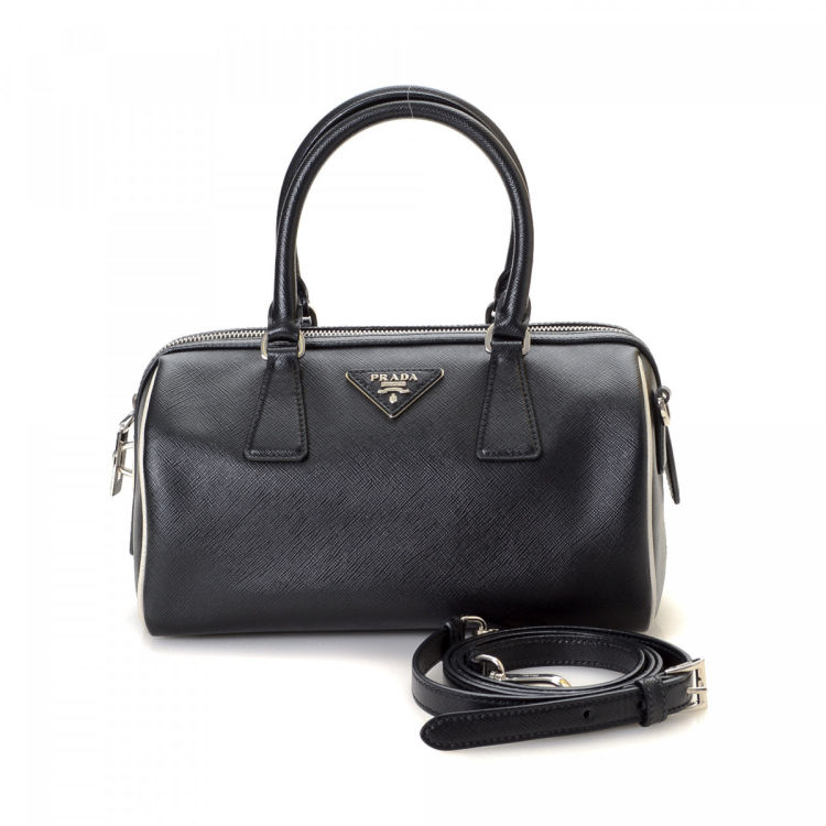 ffcb6a6dff0f The authenticity of this vintage Prada Two Way handbag is guaranteed by  LXRandCo. Crafted in saffiano leather, this classic handbag comes in black.