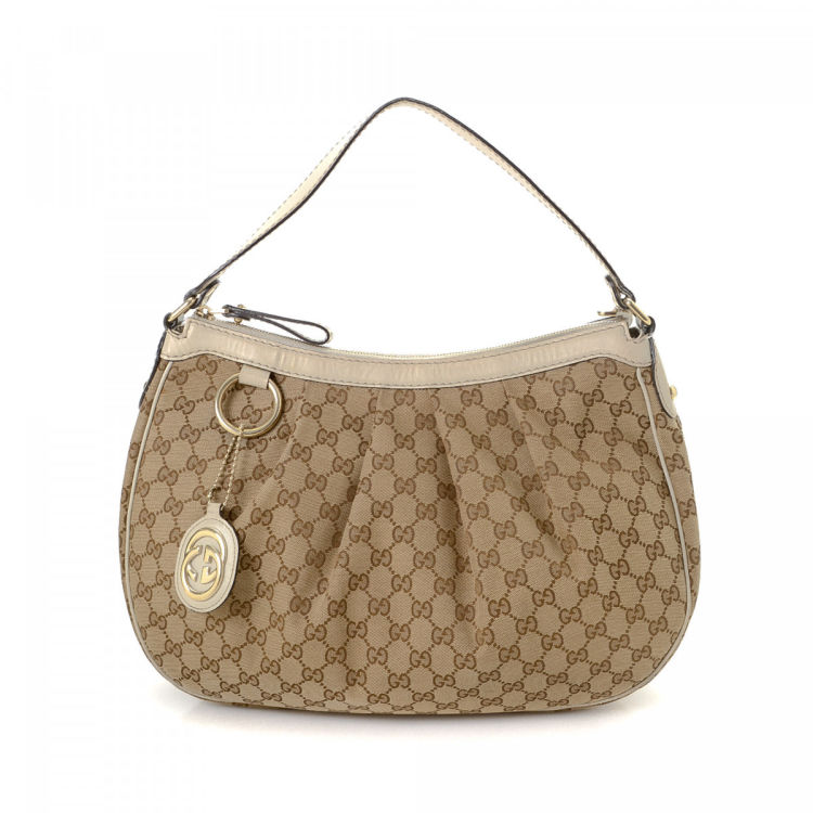 447b37838ba LXRandCo guarantees the authenticity of this vintage Gucci Sukey Hobo Bag  shoulder bag. This beautiful shoulder bag in beige is made in gg canvas.