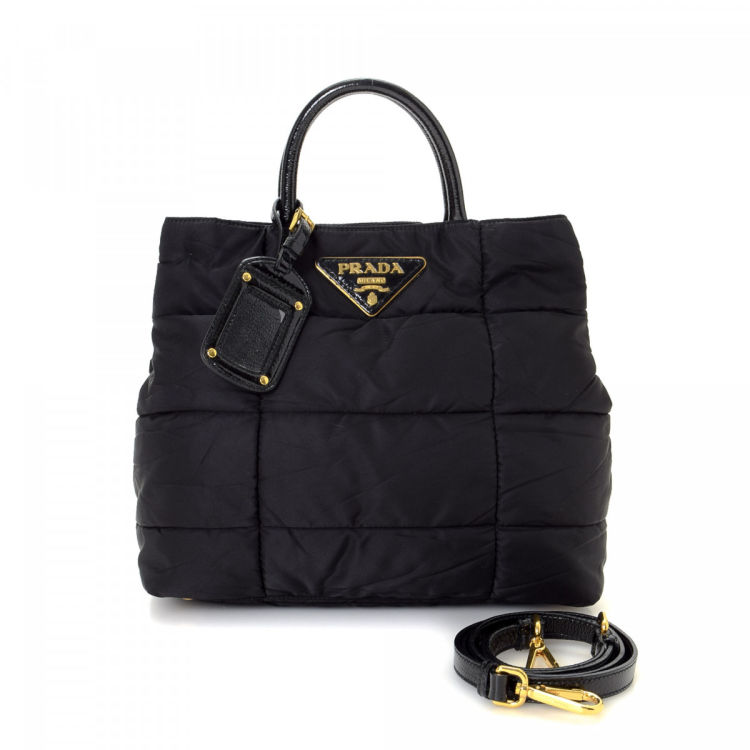 e0c6a8715d1e The authenticity of this vintage Prada Two Way handbag is guaranteed by  LXRandCo. This stylish bag in beautiful black is made in tessuto nylon.
