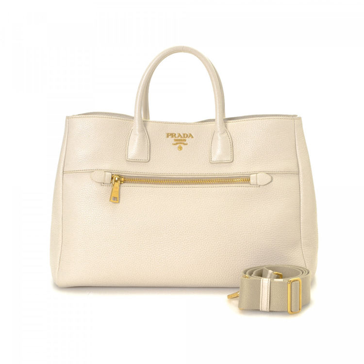 a47d50147399 LXRandCo guarantees the authenticity of this vintage Prada Vitello Two Way  tote. This elegant bag in ivory is made in vitello daino leather.