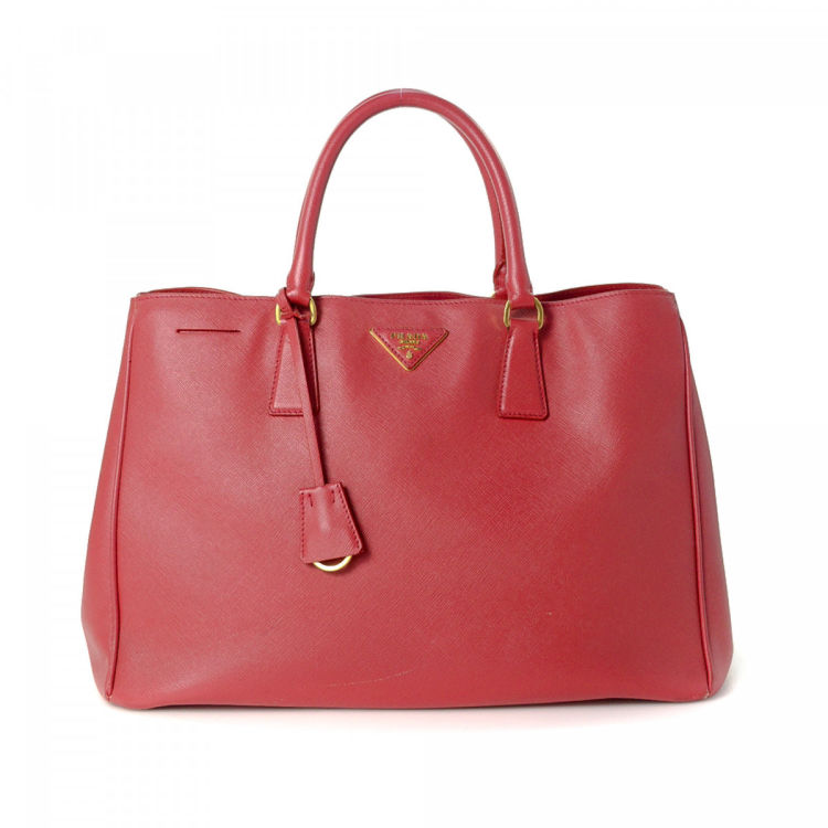 LXRandCo guarantees this is an authentic vintage Prada Promenade tote. This exquisite  tote bag was crafted in saffiano leather in red. Due to the vintage ... 26bd232f8bed5