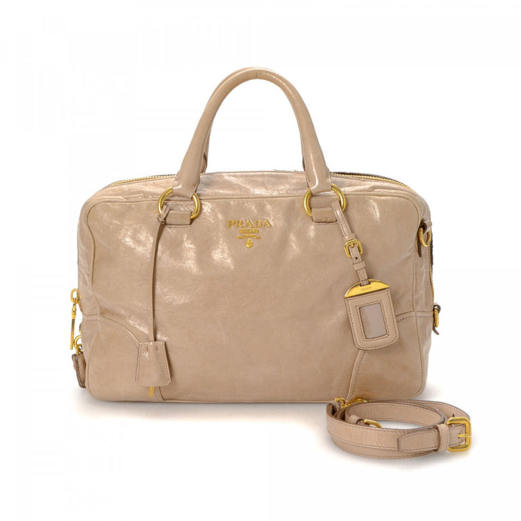 360a6f0b619b The authenticity of this vintage Prada Two Way handbag is guaranteed by  LXRandCo. This signature purse in beautiful beige is made in vitello shine  leather.