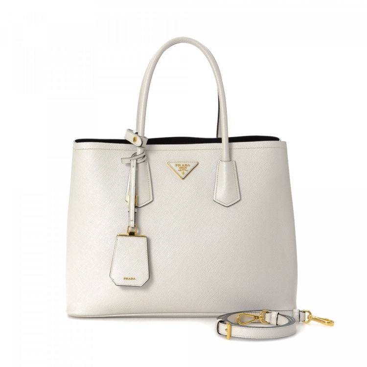 4aced40a714f LXRandCo guarantees this is an authentic vintage Prada Two Way tote. This  practical bag in white is made in saffiano leather. Due to the vintage  nature of ...