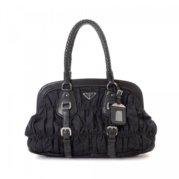 73f3eaad11a399 The authenticity of this vintage Prada shoulder bag is guaranteed by  LXRandCo. This signature purse was crafted in tessuto gaufre nylon in black.