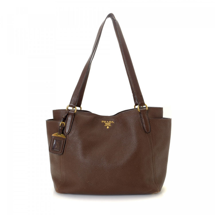 d0bcfb9c33ba2 LXRandCo guarantees this is an authentic vintage Prada tote. This classic tote  bag in brown is made in vitello daino leather. Due to the vintage nature of  ...