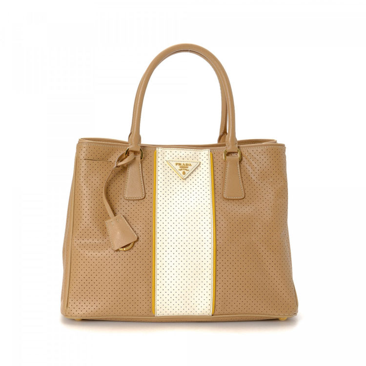 60c67194f8ed The authenticity of this vintage Prada Perforated tote is guaranteed by  LXRandCo. This lovely work bag was crafted in saffiano leather in beautiful  beige.