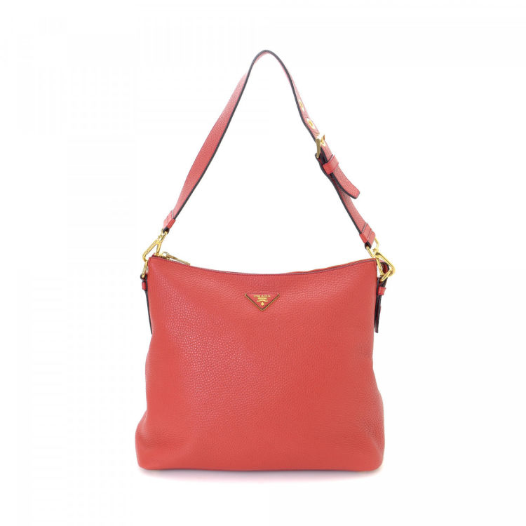 a22b57605021 LXRandCo guarantees the authenticity of this vintage Prada shoulder bag.  This practical shoulder bag in red is made in vitello daino leather.