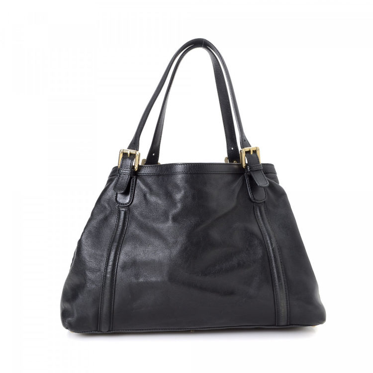 3260ee32a9a The authenticity of this vintage Gucci Britt tote is guaranteed by LXRandCo.  This iconic tote bag comes in black leather. Due to the vintage nature of  this ...