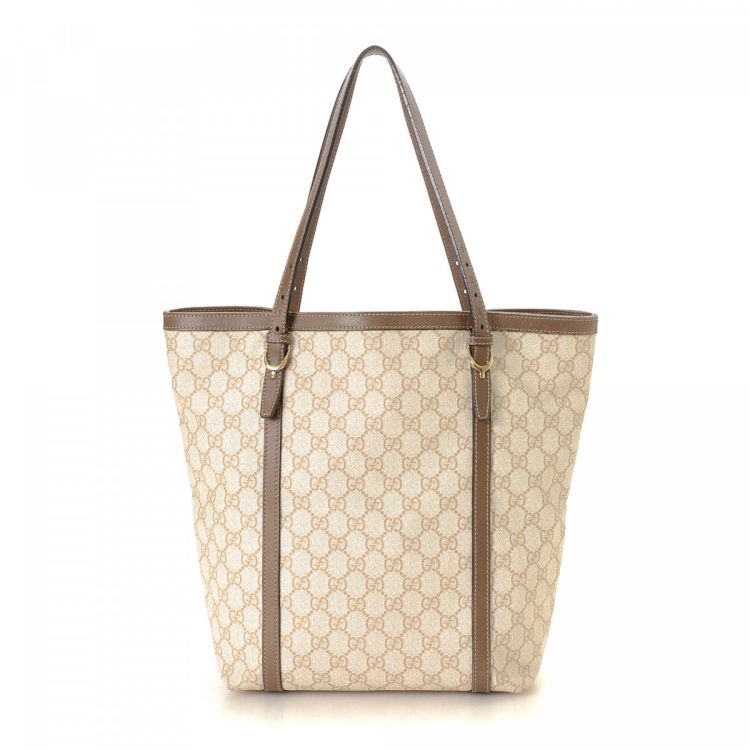 47e5a595cf24 The authenticity of this vintage Gucci Stirrup tote is guaranteed by  LXRandCo. This lovely tote bag in beige is made in gg supreme coated canvas.