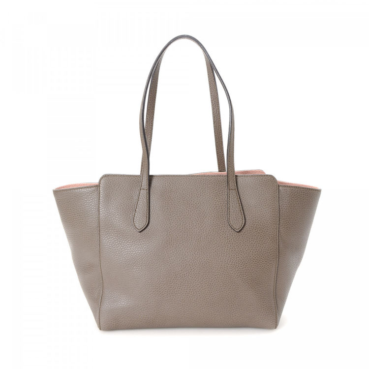 e4923e7231e2 LXRandCo guarantees the authenticity of this vintage Gucci Swing tote. This  practical work bag was crafted in leather in beautiful brown.