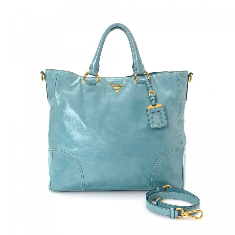 5dac74fedabc LXRandCo guarantees the authenticity of this vintage Prada Two Way tote.  Crafted in vitello shine leather, this luxurious tote comes in turquoise.