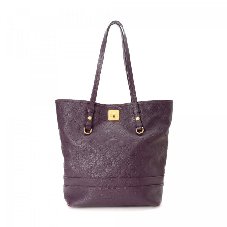 81a576d36622 LXRandCo guarantees the authenticity of this vintage Louis Vuitton Citadine  PM tote. This iconic work bag was crafted in monogram empreinte leather in .